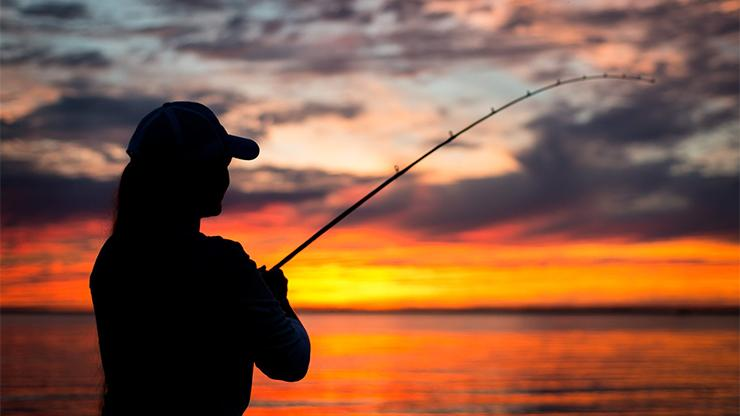 silhouette of a woman fishing at sunset