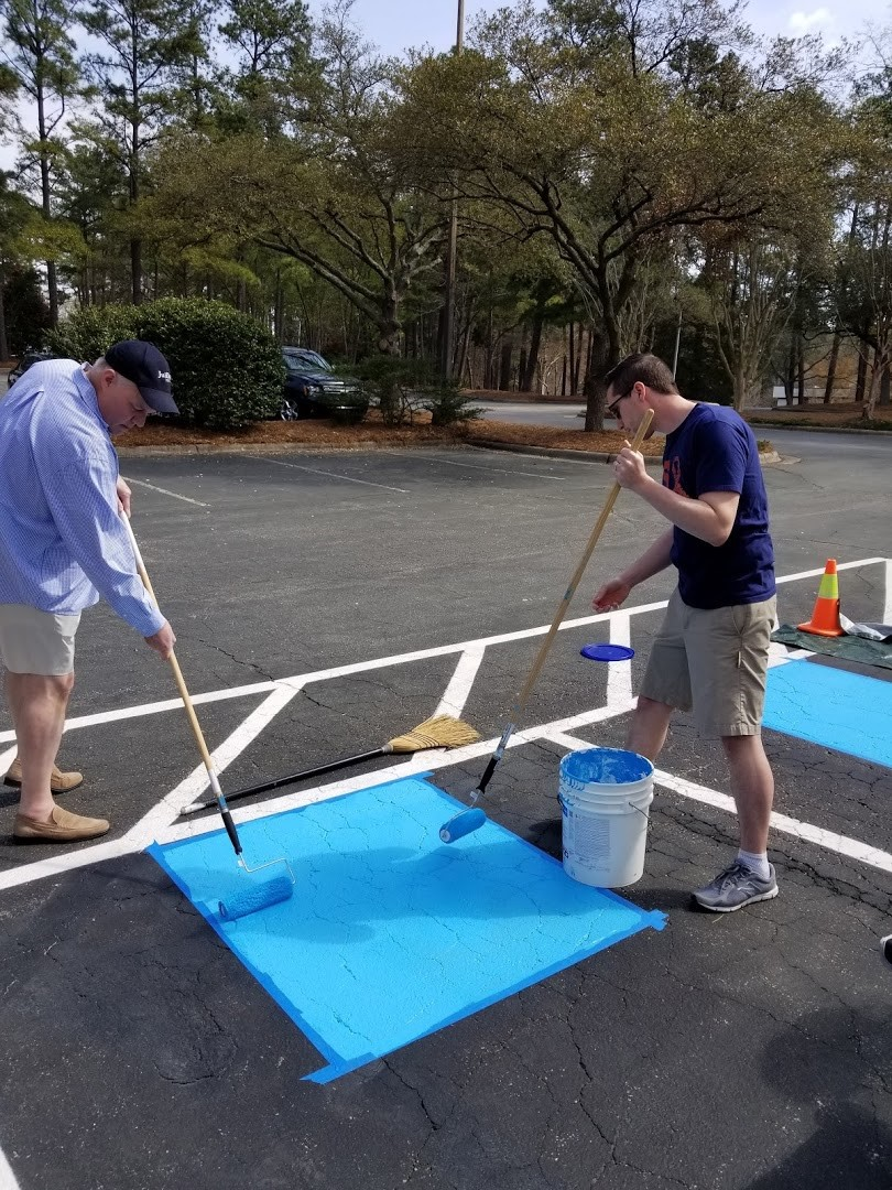 Deputy Secretary for Health Services Mark Benton and Chief of Staff for Health Services Matt Herr repaint handicap parking spaces at Raleigh's Dorothea Dix Campus.