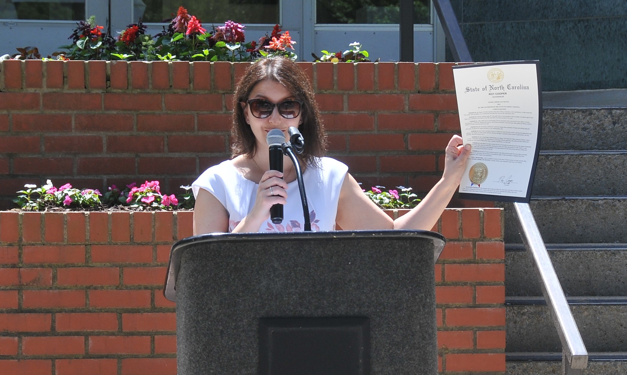 Secretary Mandy Cohen holds up Governor Cooper's Older Americans Month proclamation.