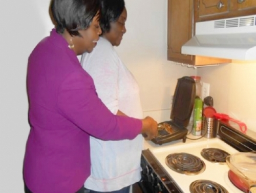 Woman Helping Blind Woman Cook