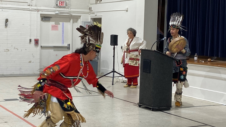 Nakaya Leviner dances while Kaya Littleturtle at the podium performs a native song.