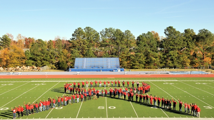 Participants from the Division of Public Health and Saint Augustine's University create a human ribbon in recognition of World AIDS Day.