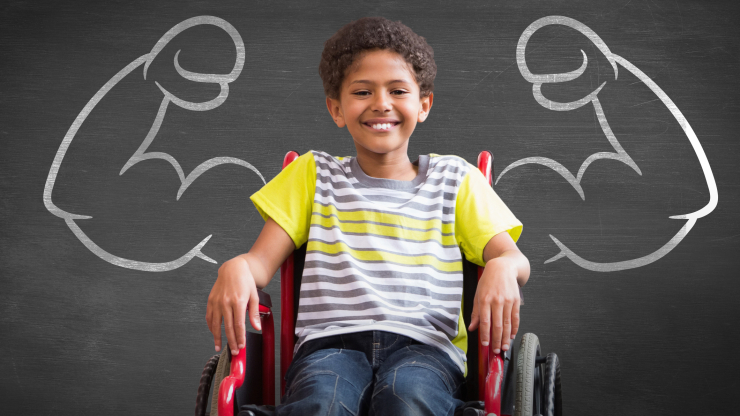A boy sits in a wheelchair in front of two muscular arms drawn on a blackboard.