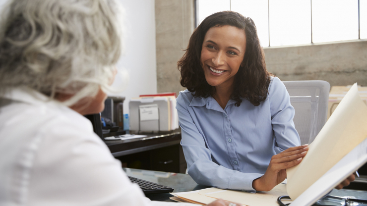 smiling female analyst in consultation with senior