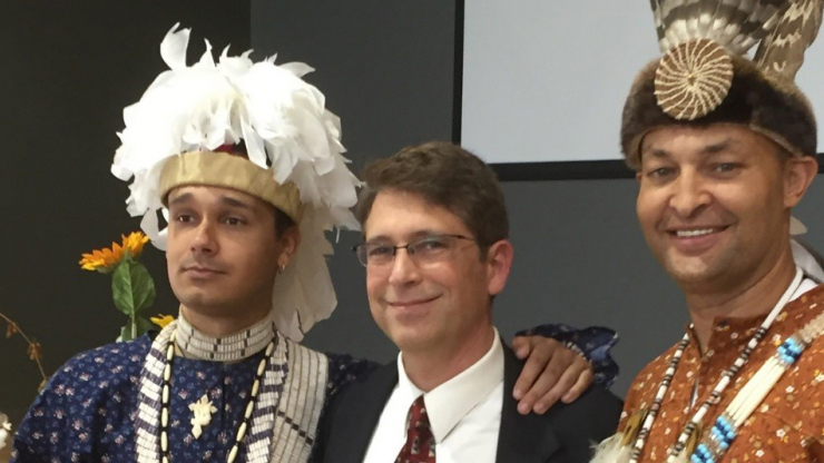 Phil Protz, Director of Program Policy Planning and Evaluation at DHHS, with Lumbee ambassadors wearing traditional attire. On the left and right of Protz are Kaya Littleturtle and John Oxendine, employees of the Lumbee tribe of North Carolina.
