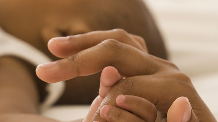 Image of an infant gripping the finger of a parent or caregiver.