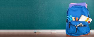 School bag in front of chalkboard