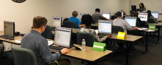 People in training class at computer workstations