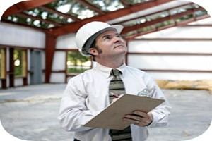 Man with clipboard and hard hat, inspecting a large building
