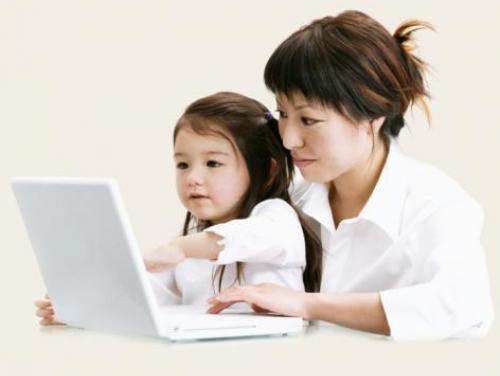 mother and young daughter using laptop