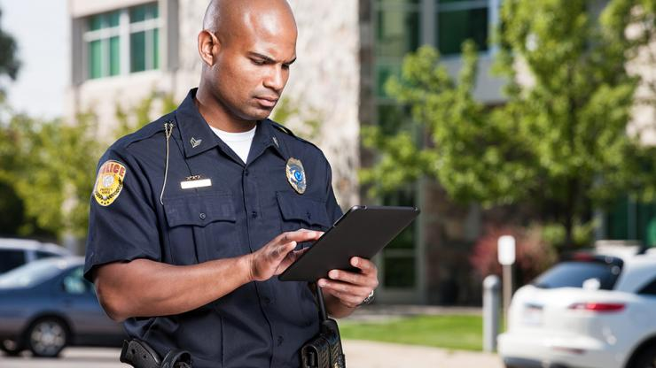 police officer accessing data on a tablet