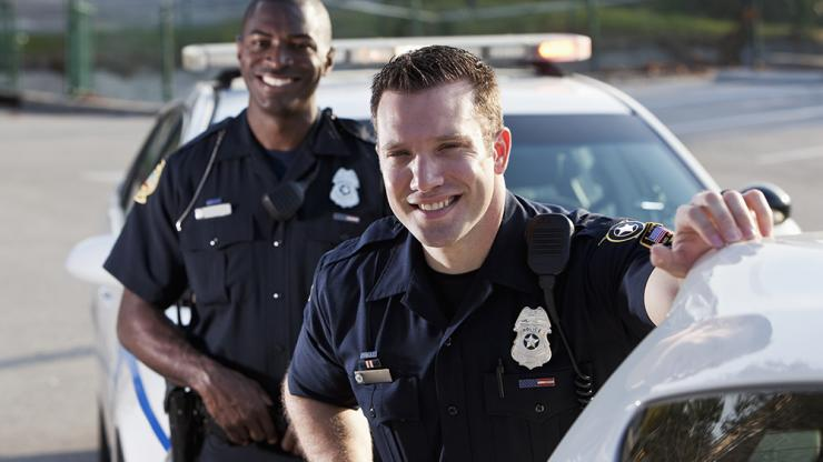 two officers standing next to patrol car