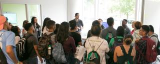 young man speaks to group of students