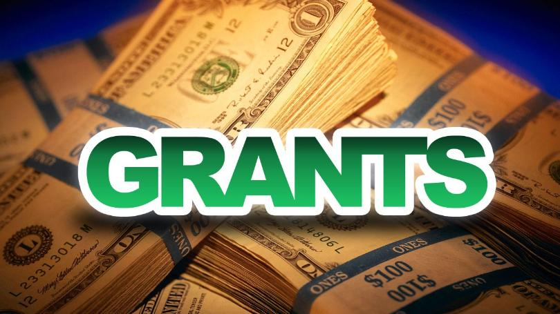 "Graphic with ""Grants"" text in bold green font with bundles of $1 bills in background"