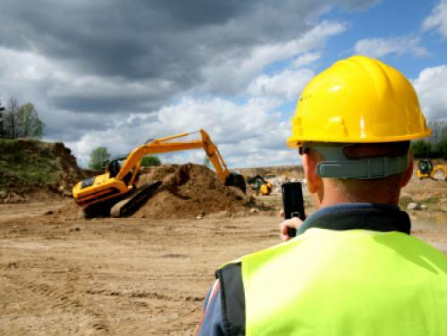 Construction worker supervising bulldozer workers on construction site.