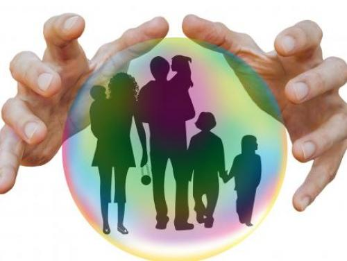 Hands hovering over a crystal ball that shows a silhouette of a large family..