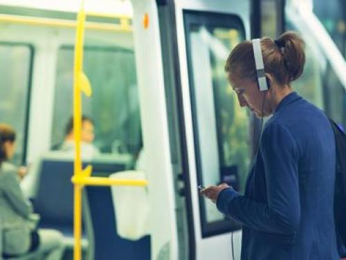Woman wearing headphones about to step onto a subway