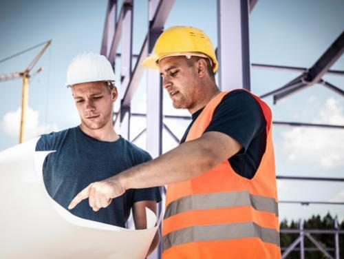 Two male construction workers talking over a blueprint