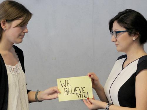 "Two women holding a poster saying ""We believe you."""