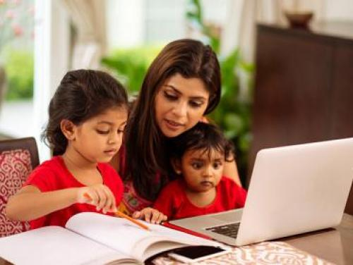 Mom sitting with children in front of a computer