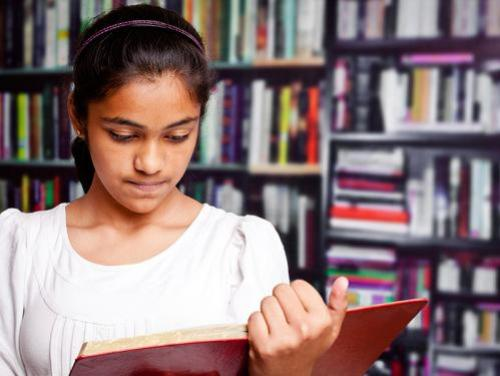 Girl reading a book in front of bookshelf