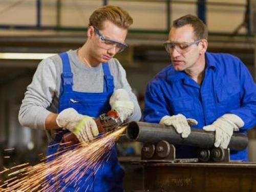 Intern and mentor working with steel