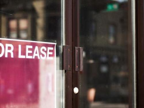"Red ""FOR LEASE"" sign on building door"