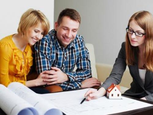 Couple looking at blueprints with a realtor