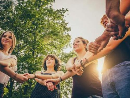 Circle of young people holding crossed arms