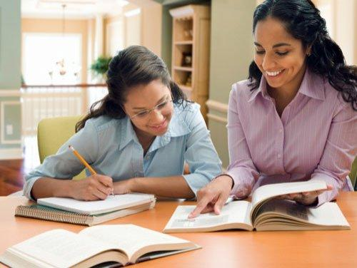 Mother and daughter studying together at a table
