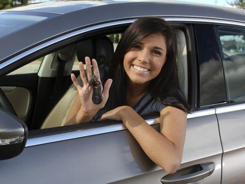 Smiling young woman driver behind the wheel inside a car