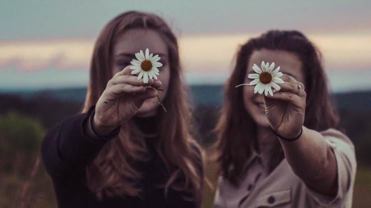Two women showing daisies