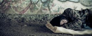 Man sleeping outside on a folded piece of foam