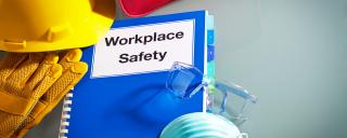 "A blue notebook says ""workplace safety"" surrounded by a first aid kid, a respiratory mask and a hard hat."