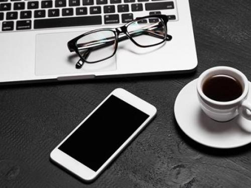 laptop, smartephone, eyeglasses and cup of coffee on a desk