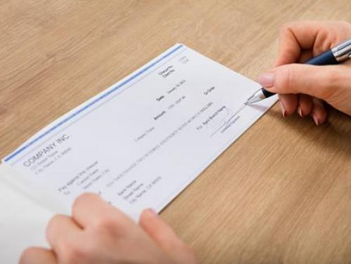 woman signing a company check