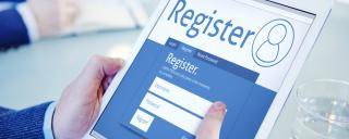 Man holding iPad and completeing online registration
