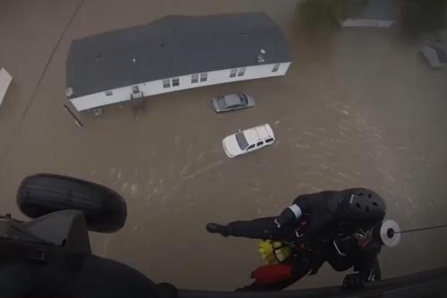 man dangling from helicopter over flooded house