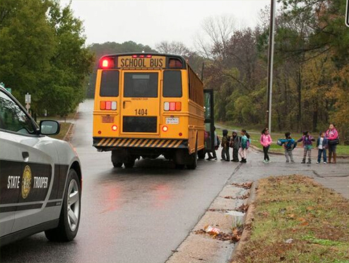 patrol car stopped behind school bus while children board