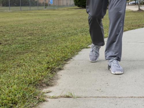 legs of someone walking down sidewalk