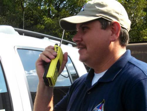 Man in NCEM hat talking on handheld radio
