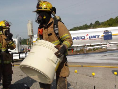 Firefighter carrying sealed drum away from leaking tanker