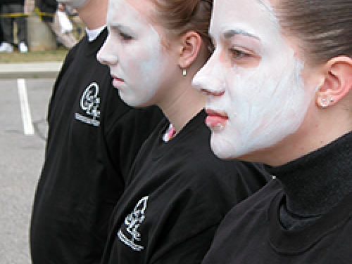 three teens with faces painted white