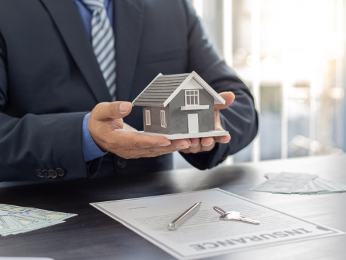 """Man in suit holding a miniature model of a house. A paper with """"Insurance"""" in big bold letters sits on the table in front of the man."""