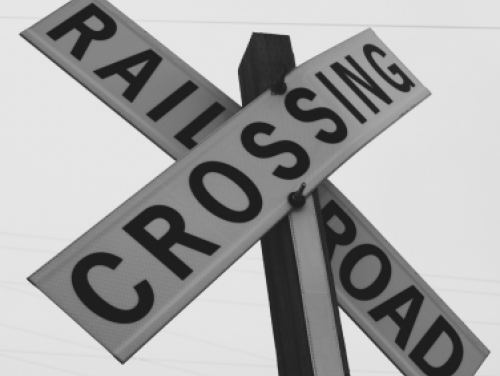 While Railroad Crossing sign with black lettering