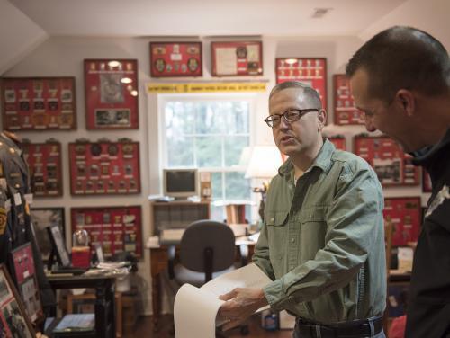 Two men standing in room full of framed SHP artifacts.