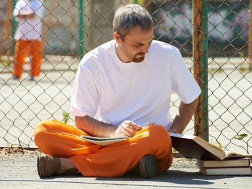 Prison inmate sitting outside & reading
