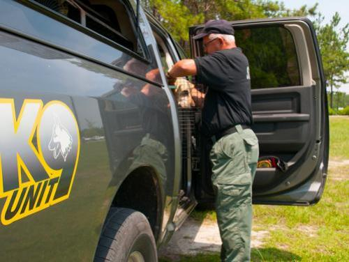 K9 officer standing outside of pickup truck