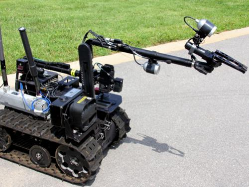 Robot on treads with arm extended reaching for something