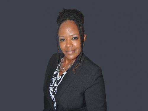 YDC Director Tangi Jordan in black suit jacket on grey background